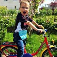 Foto: kleiner Radfahrer mit blauem Beutel am Bauch