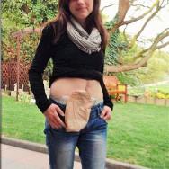 Foto: junge Frau im Garten, mit Beutel am Bauch