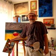Foto: Maler steht in seinem Atelier mit sichtbarem Stoma-Beutel am Bauch