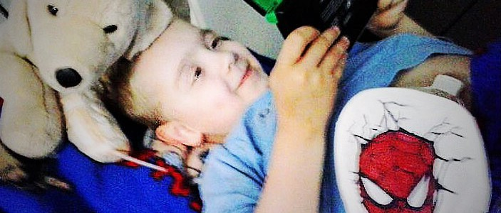Foto: Junge mit Stoma liegt im Bett und spielt auf der Spielekonsole
