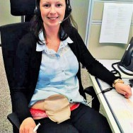 Foto: junge Stomaträgerin arbeitet im Büro und zeigt ihren Versorgungs-Beutel