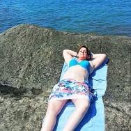 Foto: Stomaträgerin sonnt sich bauchfrei am Meer und zeigt ihren Beutel am Bauch