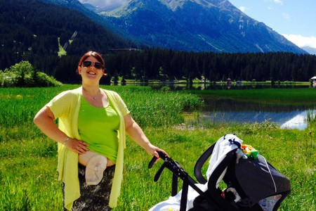 Foto: Mit ihrem Baby im Kinderwagen geht eine junge Stomaträgerin spazieren und zeigt ihren Stomabeutel am Bauch