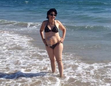 Foto: Stomaträgerin beim Baden im Meer, mit Stomabeutel am Bauch